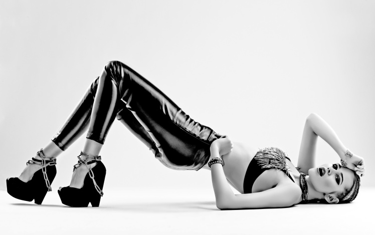 sexy woman in leather pants laying down on a white background